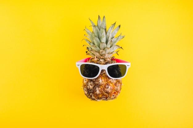 Concept de l'été. ananas mignon et drôle avec des lunettes de soleil sur fond jaune.