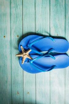 Concept d'été - chaussons de plage bleus sur plancher en bois bleu. vue de dessus
