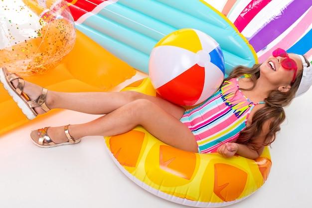 Concept d'été, fille assise autour d'un matelas pneumatique et balles de natation