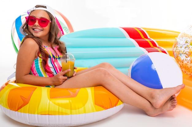 Concept d'été, fille bronzée assise autour de matelas pneumatiques, cercles et balles de natation