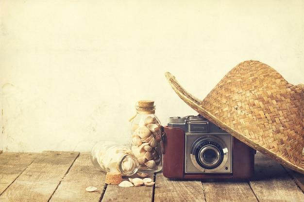 Concept d'été ou de vacances. chapeau de paille avec vieille caméra vintage et coquilles sur fond en bois.
