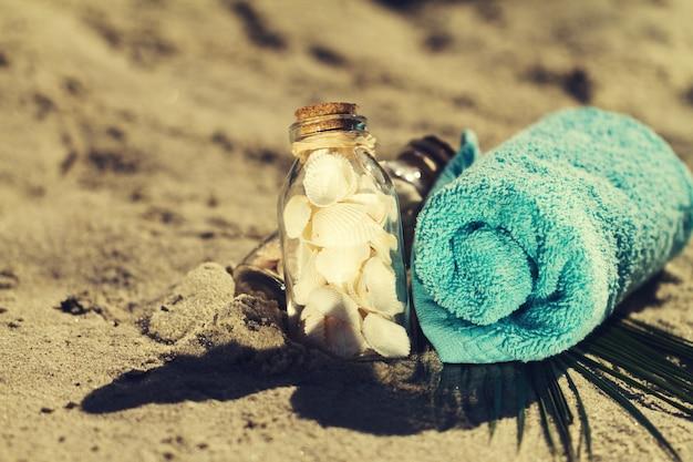 Concept d'été ou de vacances. coquillages en bouteilles sur sable avec une serviette bleue. toning.