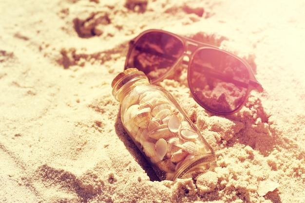 Concept d'été ou de vacances. des coquillages en bouteilles sur sable. toning.