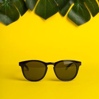 Concept d'été et de vacances. lunettes de soleil et feuilles tropicales sur fond de couleur jaune