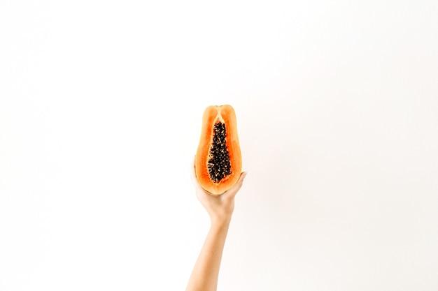 Concept d'été et de voyage. la main de la jeune femme tenant des fruits de papaye orange tropicale exotique