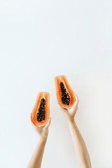 Concept d'été et de voyage. les mains de la jeune femme tenant des fruits de papaye orange tropicale exotique. végétarien saisonnier minimaliste