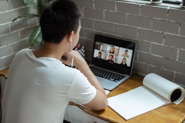 Concept d'étude en ligne l'étudiant universitaire essayant d'expliquer son opinion sur le sujet qu'il conclut sur le cahier pendant que ses camarades de classe l'écoutent.