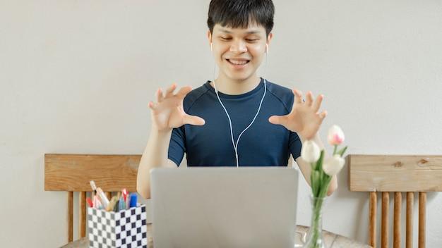 Concept d'étude en ligne le gars du collège avec un large sourire terminant son projet difficile après l'avoir fait pendant plusieurs semaines.