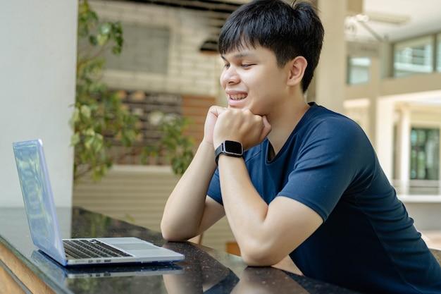 Concept d'étude en ligne l'homme portant une chemise bleu foncé assis sur la chaise en bois et essayant de sortir d'une idée créative à ajouter à son nouveau projet.