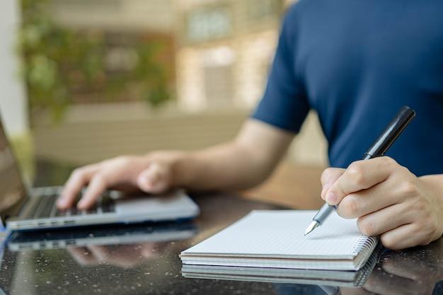 Concept d'étude en ligne de l'homme qui travaille à domicile et tente de rédiger le rapport de la réunion pendant la réunion en ligne de son entreprise.