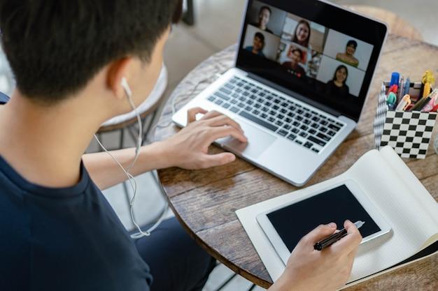 Concept d'étude en ligne le jeune homme d'entreprise qui met un ordinateur portable sur la table en bois étant occupé à faire faire la liste de contrôle sur le livre en l'écrivant sur son appareil technologique.