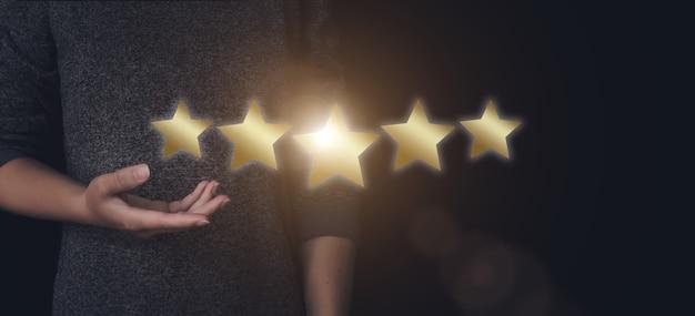 Le concept d'évaluation. une main pointant vers cinq étoiles augmente la note de l'entreprise