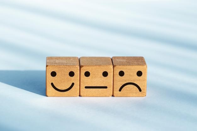 Concept d'évaluation de service. évaluation des commentaires. icône de smiley sur des dés en bois