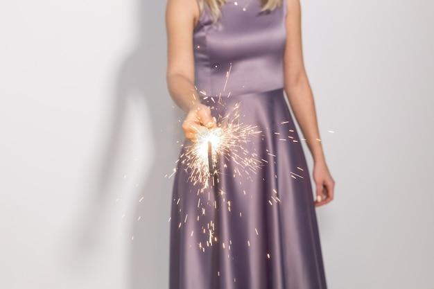 Concept d'événement, de célébration et de vacances - gros plan des mains de femme tenant un cierge magique.
