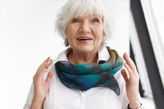 Concept d'excitation, de joie, de succès et d'émotions positives. heureuse femme européenne extatique ravie à la retraite s'exclamant d'être étonné et excité avec un cadeau d'anniversaire, faisant des gestes avec émotion