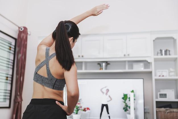 Concept d'exercice sain à la maison, femme asiatique en forme, rester à la maison et s'entraîner à la télévision en ligne à la maison, nouvelle vie normale de l'épidémie de covid-19