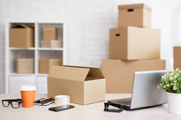 Concept d'expédition et de livraison - table avec ordinateur portable et boîtes d'expédition au bureau de poste