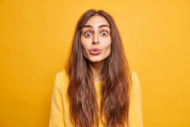 Concept d'expressions de visage humain. une jolie femme surprise aux longs cheveux noirs garde les lèvres pliées