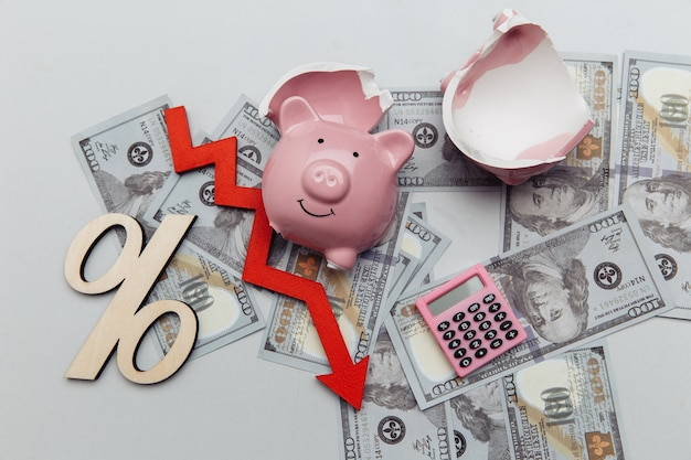 Concept de faillite tirelire cassée sur les billets en dollars et flèche vers le bas sur les billets en argent