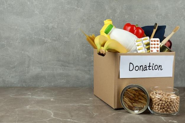 Concept de faire un don avec une boîte de dons sur une table texturée grise
