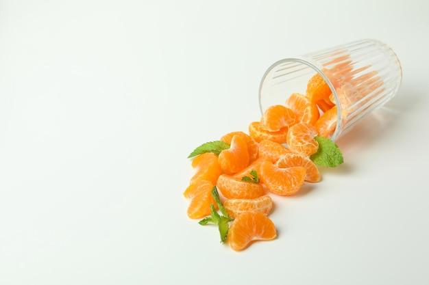 Concept de faire du jus de mandarine avec du verre avec des mandarines sur fond blanc.
