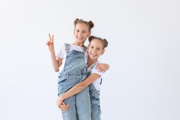 Concept de famille et d'amour - deux soeurs jumelles souriantes étreignant sur un mur blanc.