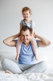 Concept de famille, d'amour et de paternité - père heureux s'amusant avec sa jolie petite fille à la maison