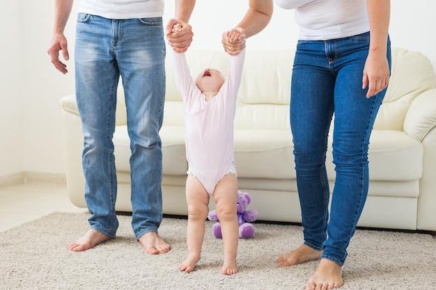 Concept de famille, d'enfants et de parentalité - parents apprenant à une petite fille à marcher.