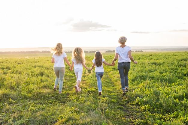 Concept de famille, d'été et de vacances - groupe de femmes et de filles partant dans un champ vert
