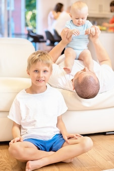 Le concept de famille, le garçon est assis sur le sol à la recherche, le prochain père joue sur le canapé avec le bébé, l'enfant est assis sur la poitrine de son père, enfance heureuse, famille
