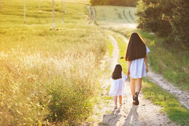 Concept de famille heureuse. maman et bébé se tenant la main et marchant le soir dans les rayons du beau coucher de soleil. petites promenades avec sa mère sur la route. champ jaune, soleil couchant, jour et soir d'été