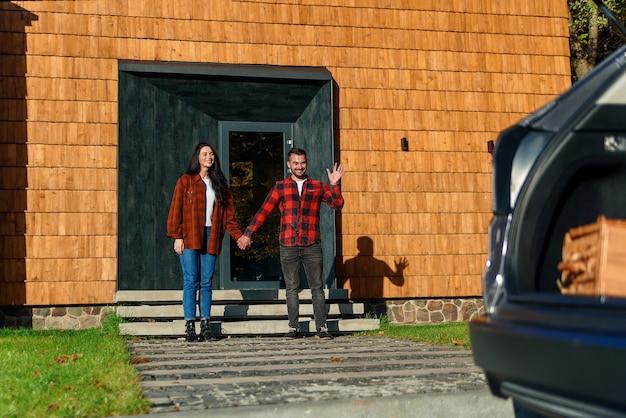 Concept de famille heureuse. maman et papa sur le porche de la maison leur attendent leurs enfants qui courent.