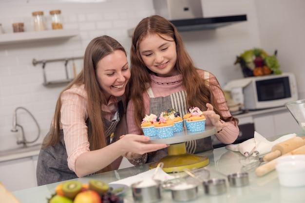 Concept de famille heureuse d'une mère et de sa fille dégustant des cupcakes ensemble dans la cuisine à la maison.