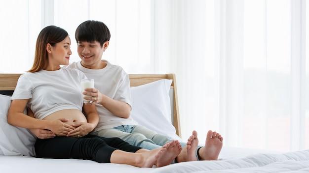 Concept de famille heureuse et saine. photo d'un jeune couple assis sur un lit ensemble. un jeune mari souriant et tenant un verre de lait et le donnant avec amour à une femme enceinte.