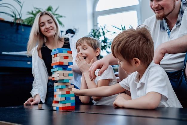 Concept de famille, ils passent du temps ensemble et s'amusent. des frères joyeux et leurs parents jouent au jeu de jenga dans le salon.