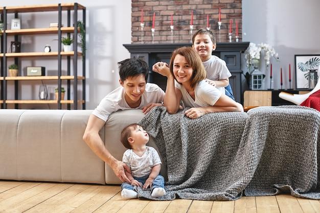 Concept de famille internationale heureuse. papa, maman, fils et petite fille posant pour un appareil photo à la maison sont engagés dans la parentalité à domicile. vacances à la maison, parentalité, concept enfants et parents.