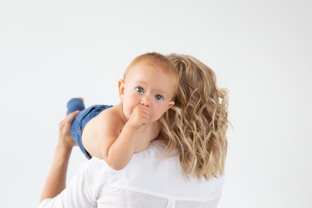 Concept de famille, maternité et famille - jeune mère tenant son bébé sur un mur blanc