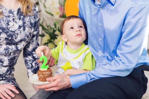 Concept de famille, de parentalité, de joyeux anniversaire et de vacances - gros plan heureux parents et enfant à table buvant du thé et mangeant du gâteau