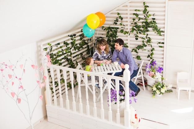 Concept de famille, de parentalité, de joyeux anniversaire et de vacances - parents et enfants heureux à une table buvant du thé et mangeant du gâteau.
