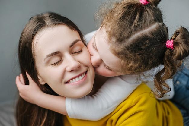 Concept de famille de personnes relatives. mignon adorable drôle enfant fille embrassant sur la joue jeune maman jouant sur le lit à la maison, mère souriante ou nounou reste prendre, petite fille profiter d'un moment tendre avec maman, amour