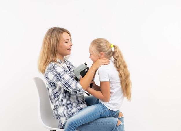 Concept de famille, de photographie et de passe-temps - femme et son enfant utilisant un appareil photo à l'ancienne sur fond blanc.