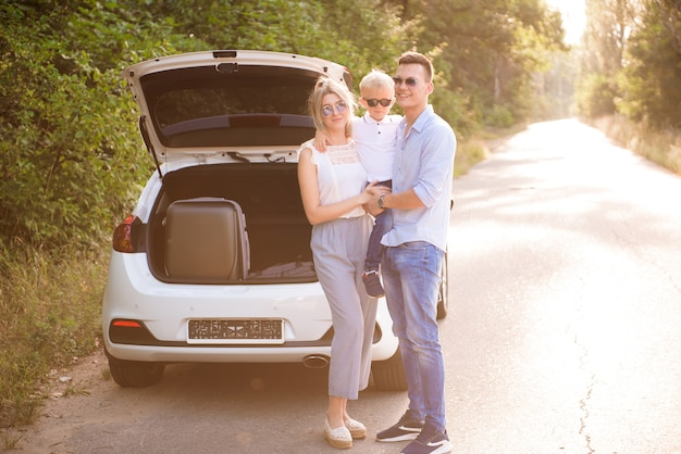 Concept de famille, transport, sécurité, voyage sur la route et personnes - heureux homme et femme avec petit enfant voyage.
