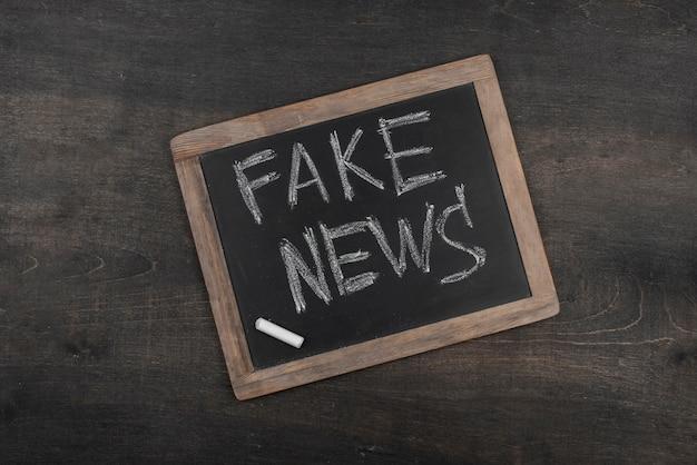 Concept de fausses nouvelles avec vue de dessus de tableau noir