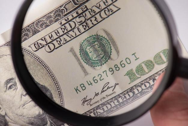 Concept de faux argent. photo en gros plan recadrée d'un humain trouvant de faux billets en regardant à travers une loupe