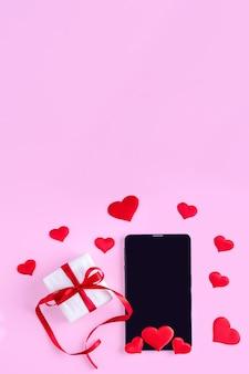 Concept de félicitations en ligne. tablette vierge noire ou écran de téléphone avec forme de coeur rouge et cadeau