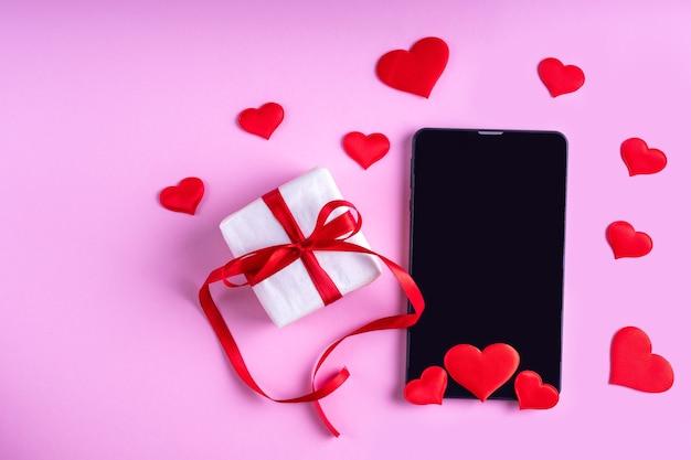 Concept de félicitations en ligne. tablette vierge noire ou écran de téléphone avec forme de coeurs rouges et cadeau