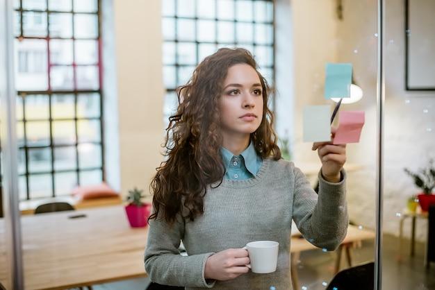 Concept de femme d'affaires faisant des plan sur des notes autocollantes.