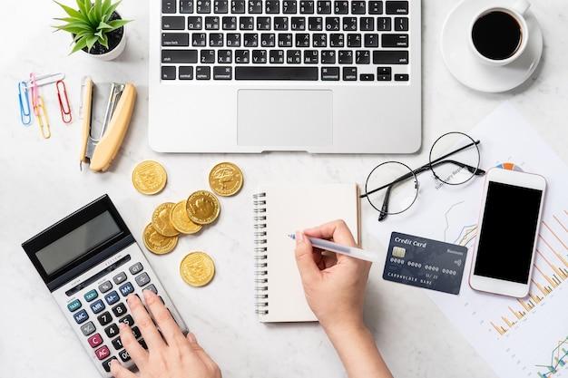 Concept d'une femme faisant le paiement en ligne avec carte et smartphone isolé sur une table de bureau en marbre moderne, maquette, vue de dessus, espace copie, mise à plat, gros plan