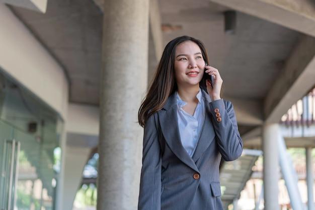 Concept de femme qui travaille une femme d'affaires appelant avec le client au sujet de l'entreprise à l'extérieur du bureau.