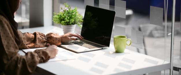 Concept de femme qui travaille: femme écrivant une note alors qu'il travaillait avec un ordinateur portable